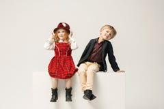 Enfants élégants mignons sur le fond blanc de studio Photos stock