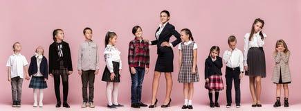 Enfants élégants mignons sur le fond rose de studio Les beaux filles et garçon de l'adolescence se tenant ensemble photographie stock