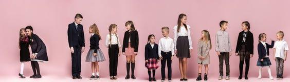 Enfants élégants mignons sur le fond rose de studio Les beaux filles et garçon de l'adolescence se tenant ensemble image stock