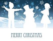 Enfants établissant la scène de Noël de bonhomme de neige Photos stock