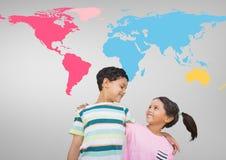 Enfants étreignant devant la carte colorée du monde Photographie stock