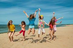 Enfants actifs heureux sautant sur la plage Image stock