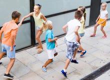 Enfants activement jouant et courant ensemble sur la rue l'été d Photo libre de droits