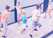 Enfants activement jouant et courant ensemble sur la rue l'été d Image libre de droits