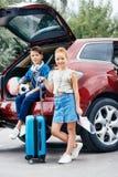 enfants adorables avec le bagage se tenant à côté de la voiture Photographie stock libre de droits