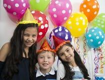 Enfants adorables ayant l'amusement à la fête d'anniversaire Image libre de droits