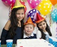 Enfants adorables ayant l'amusement à la fête d'anniversaire Photographie stock libre de droits