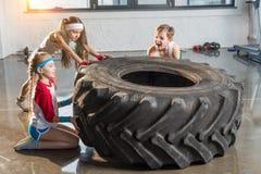 Enfants adorables dans la formation de vêtements de sport avec le pneu au studio de forme physique photo libre de droits