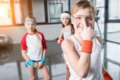 Enfants adorables dans les vêtements de sport dupant autour au studio de forme physique Image libre de droits