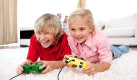 Enfants adorables jouant des jeux vidéo Images libres de droits