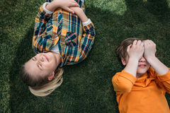 Enfants adorables prenant un bain de soleil tout en se trouvant sur l'herbe Photo libre de droits