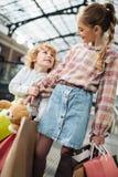 Enfants adorables tenant des sacs en papier et regardant l'un l'autre Photographie stock