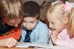 Enfants affichant un livre Photos libres de droits
