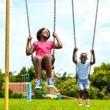 Enfants africains ayant l'amusement balançant dans le parc Image libre de droits