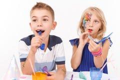 Enfants agréables soufflant des tuyaux d'anniversaire Images stock