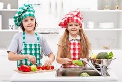 Enfants aidant dans la cuisine - lavant et découpant des légumes en tranches images stock