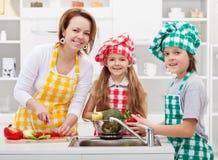Enfants aidant la mère dans la cuisine photographie stock libre de droits