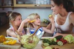 Enfants alimentant une tranche de courgette à la mère dans la cuisine Images libres de droits