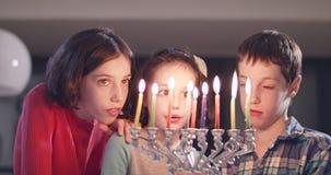 Enfants allumant des bougies de Hanoukka à la maison