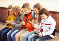 Enfants amicaux s'asseyant avec des périphériques mobiles Photo libre de droits