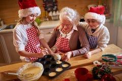 Enfants appréciant avec la grand-mère faisant des biscuits de Noël Photo libre de droits