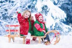 Enfants appréciant le tour de traîneau le jour de Noël Photos stock