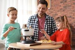 Enfants appr?ciant le d?ner de fondue avec le p?re photos stock
