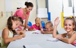 Enfants apprenant à écrire sur la leçon dans la classe d'école primaire Images stock