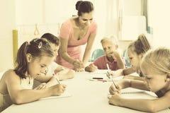 Enfants apprenant à écrire sur la leçon dans la classe d'école primaire Photos libres de droits