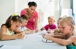 Enfants apprenant à écrire sur la leçon dans la classe d'école primaire Photo libre de droits