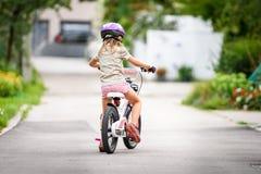 Enfants apprenant à conduire une bicyclette sur une allée dehors Photos stock