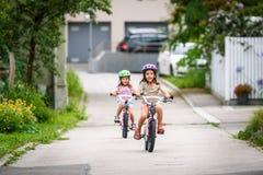 Enfants apprenant à conduire une bicyclette sur une allée dehors Photo libre de droits
