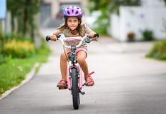 Enfants apprenant à conduire une bicyclette sur une allée dehors Photos libres de droits