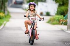 Enfants apprenant à conduire une bicyclette sur une allée dehors Image libre de droits