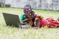 Enfants apprenant avec l'ordinateur dans le jardin à la maison image stock