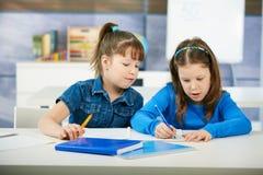 Enfants apprenant dans la salle de classe Photos stock
