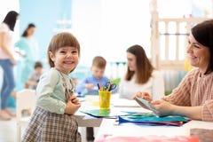 Enfants apprenant des arts et des métiers dans le jardin d'enfants avec le professeur image libre de droits