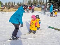 Enfants apprenant à skier au parc olympique de Canada Photos stock