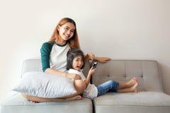 Enfants asiatiques à l'aide du smartphone se reposant ensemble sur le sofa Images libres de droits