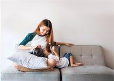 Enfants asiatiques à l'aide du smartphone se reposant ensemble sur le sofa Image stock