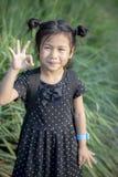 Enfants asiatiques avec le signe de sourire de visage et de main pour l'ok photos stock
