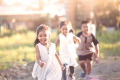 Enfants asiatiques heureux ayant l'amusement à courir et jouer ensemble Image stock