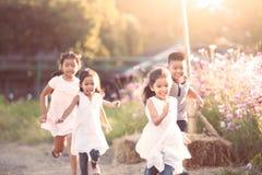 Enfants asiatiques heureux ayant l'amusement à courir et jouer ensemble Photos libres de droits