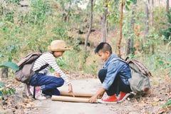 Enfants asiatiques heureux regardant une carte Photos libres de droits