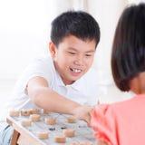 Enfants asiatiques jouant aux échecs chinois Images libres de droits