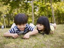 Enfants asiatiques jouant avec la loupe dehors Image stock