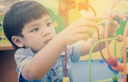 Enfants asiatiques jouant sur le jouet éducatif Image libre de droits