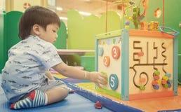 Enfants asiatiques jouant sur le jouet éducatif Photographie stock libre de droits