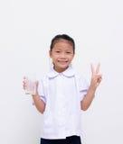 Enfants asiatiques - l'étudiant thaïlandais mangent du lait sur le fond blanc Images stock