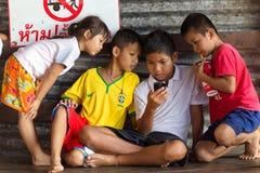 Enfants asiatiques regardant l'écran de smartphone Photos libres de droits
